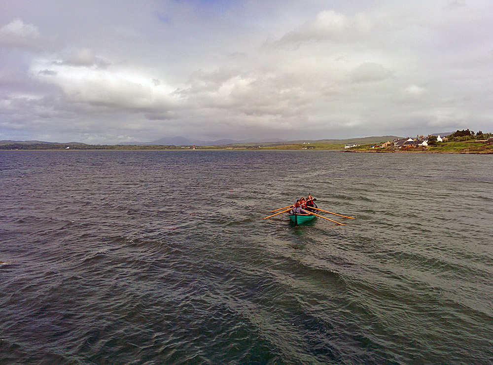Picture of a skiff being rowed on a sea loch by a school crew with their teacher