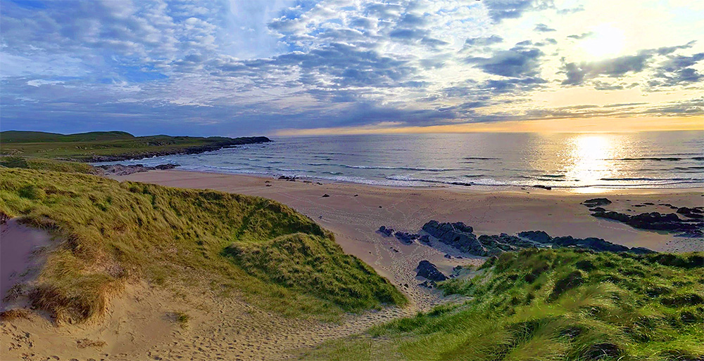 Panoramic picture of a June evening view from the top dunes above a bay with a sandy beach