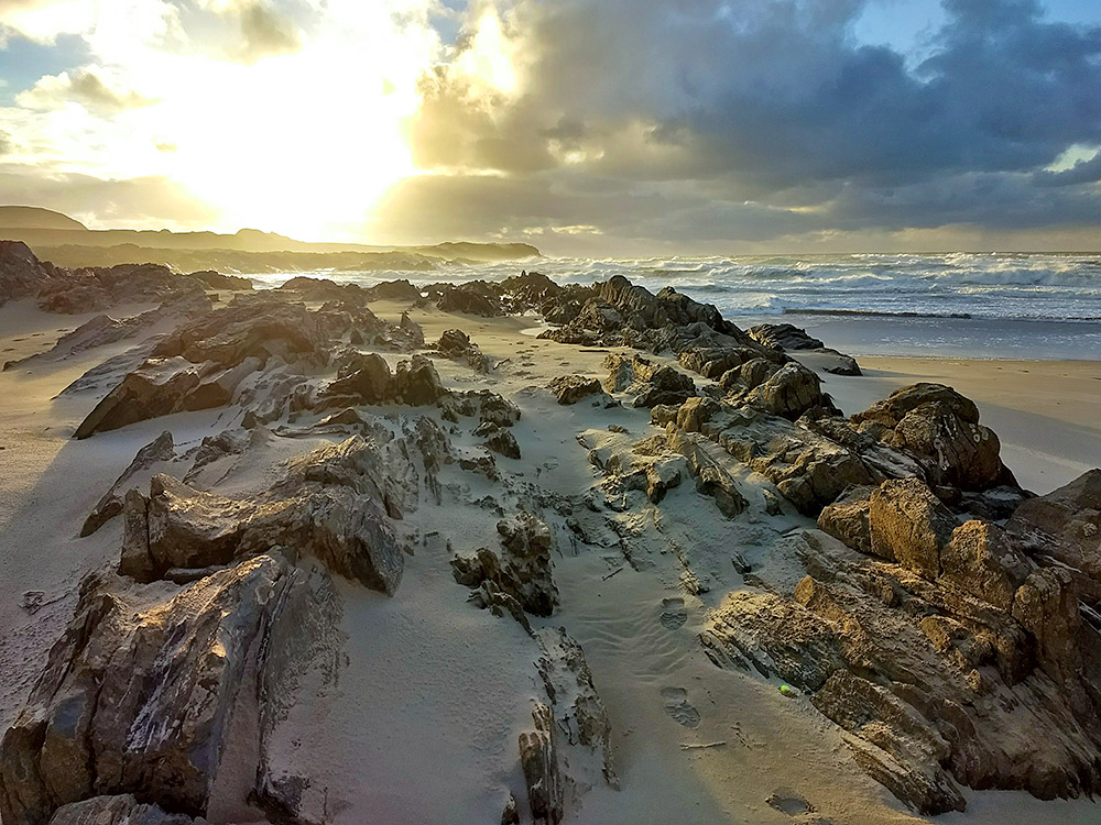 Picture of sunshine over a bay with waves rolling in onto a beach with some rocks