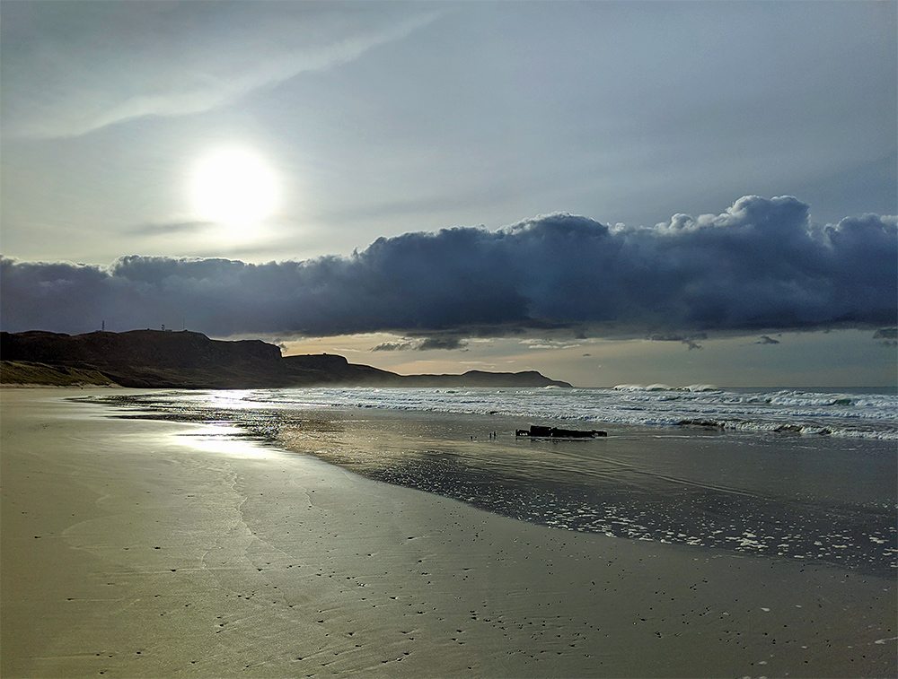 Picture of the sun over a bank of clouds at a beach with a wreck