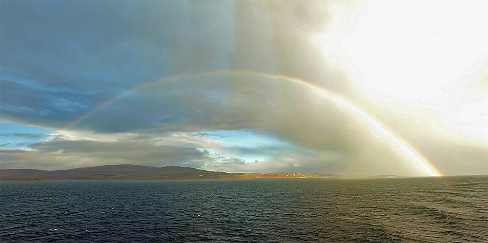 Picture of a full rainbow over the coast of an island, seen from a passing ferry