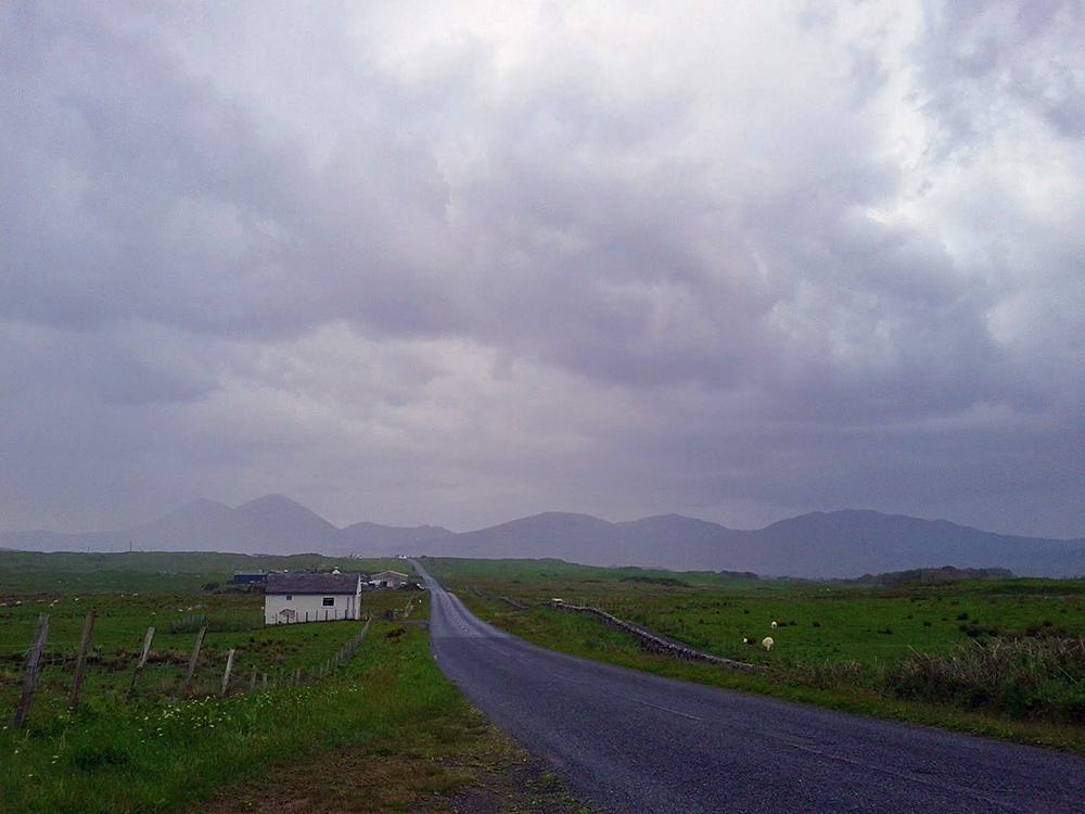 Picture of a country road on a rainy day, mountains just visible in the distance