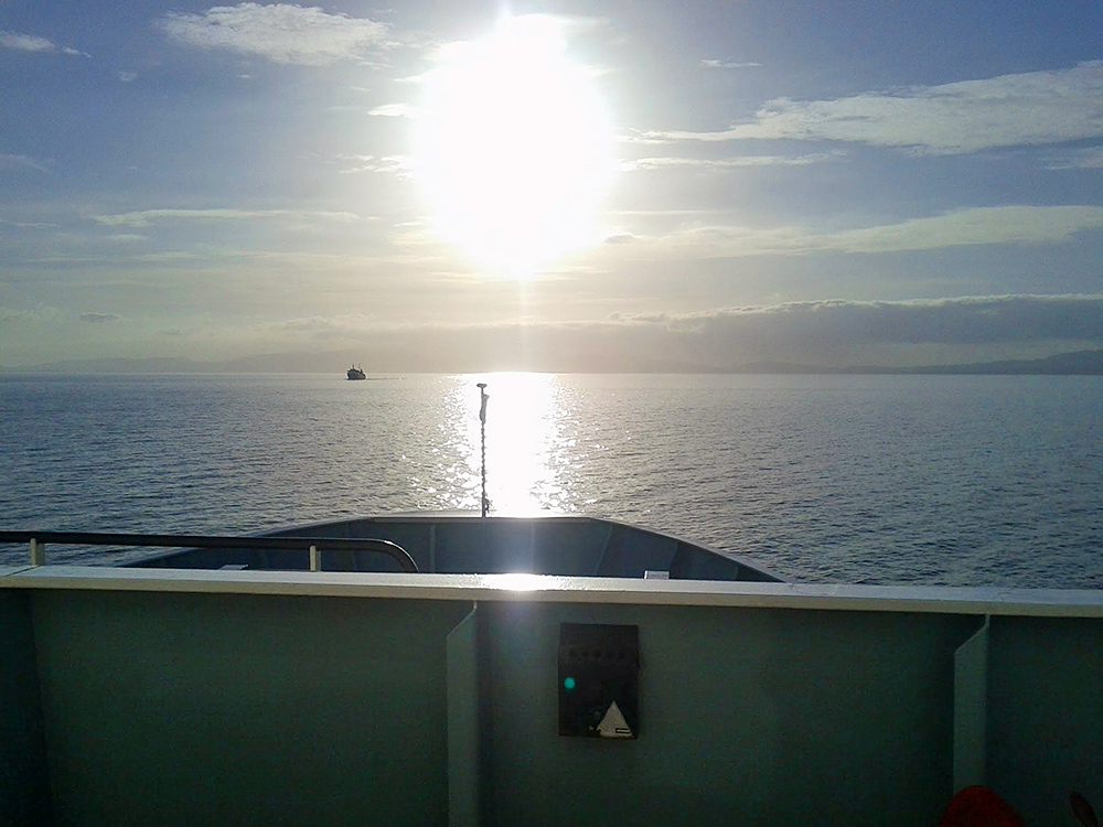 Picture of a view from the bow of a ferry travelling towards the low sun