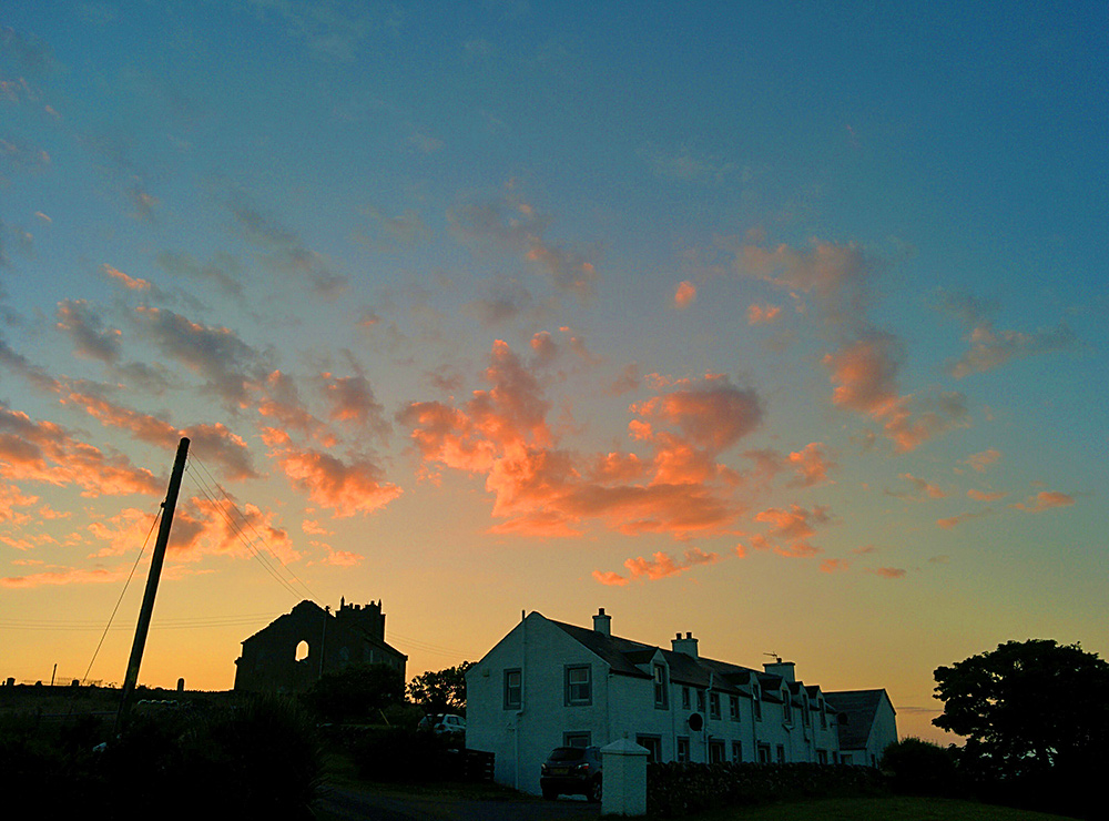 Picture of a row of cottages under a colourful evening sky
