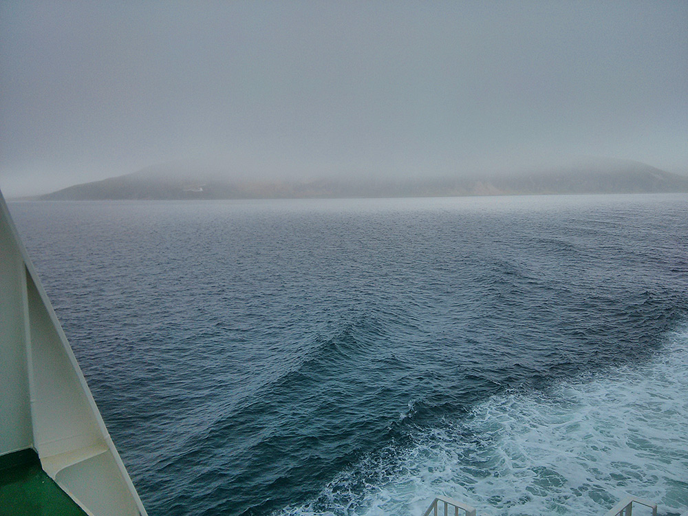 Picture of a view back from a ferry to an island under low clouds