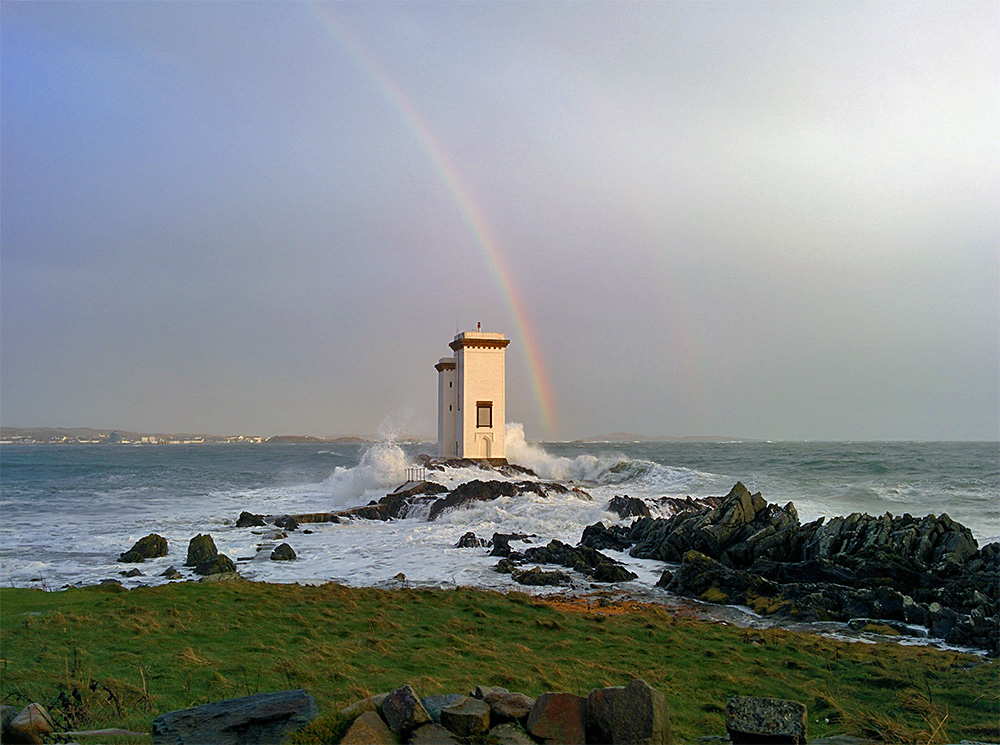 Picture of a square lighthouse on a stormy day with a rainbow behind it