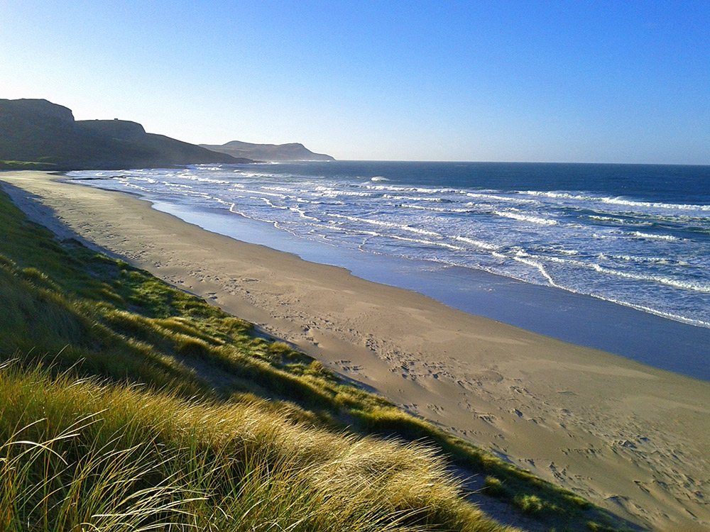 Picture of a view from some dunes over a beach and a bay with waves rolling in on a beautiful sunny October day