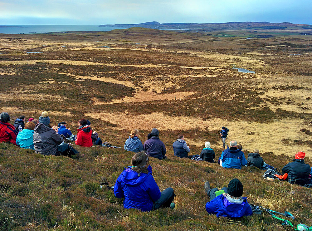 Picture of a group of walkers enjoying lunch on the side of a hill with a view over a peninsula