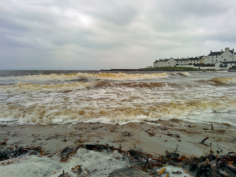 Picture of winter waves rolling on to a small beach in a coastal village