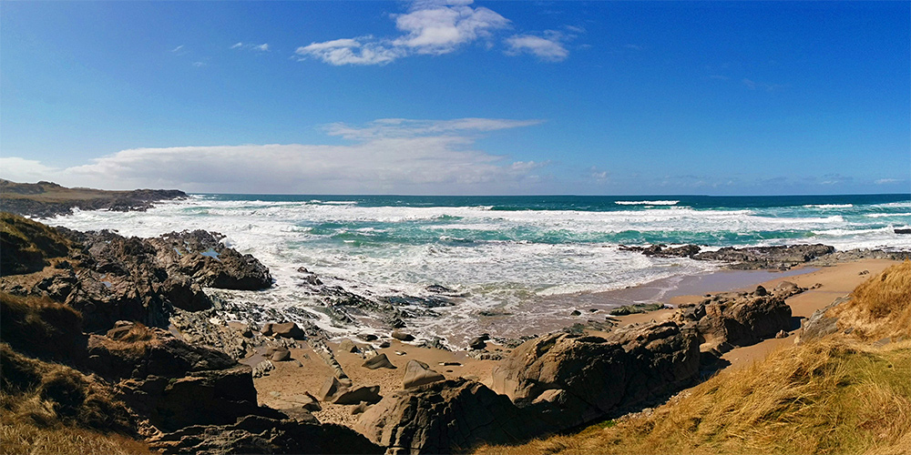Panoramic picture of waves rolling into a bay with cliffs and a sandy beach