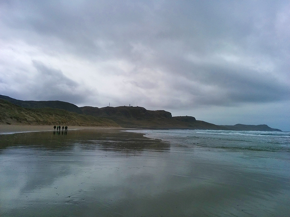Picture of a group of beach walkers on a sandy beach under heavy clouds