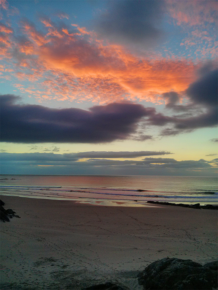 Picture of colourful clouds during a sunset over a bay with a beach