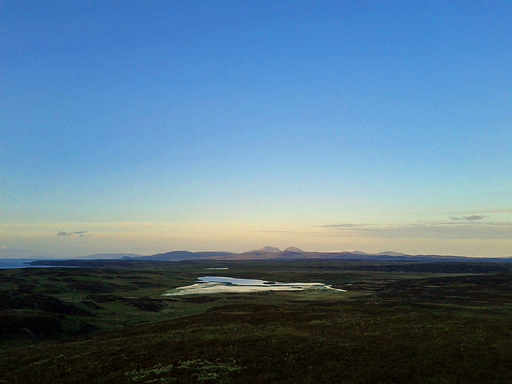 Picture of a loch (lake) and some distant mountains in the fading last light of a June evening