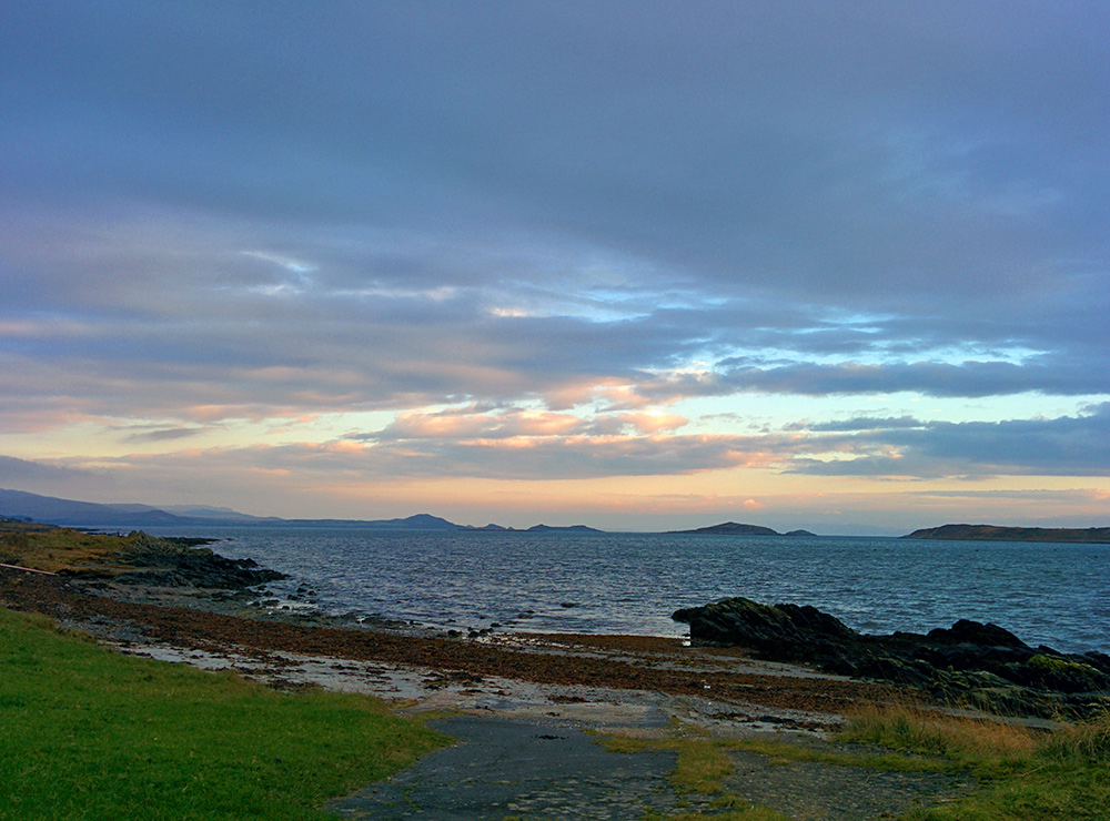 Picture of mild November morning light breaking through clouds over a bay with islands