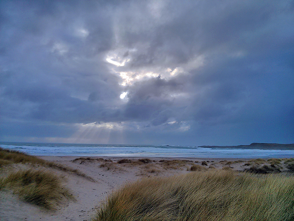 Picture of the sun breaking through clouds over a bay with a beach, seen from the dunes
