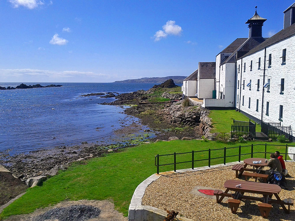 Picture of tables outside Laphroaig distillery with two visitors enjoying a drink with a view in the sun