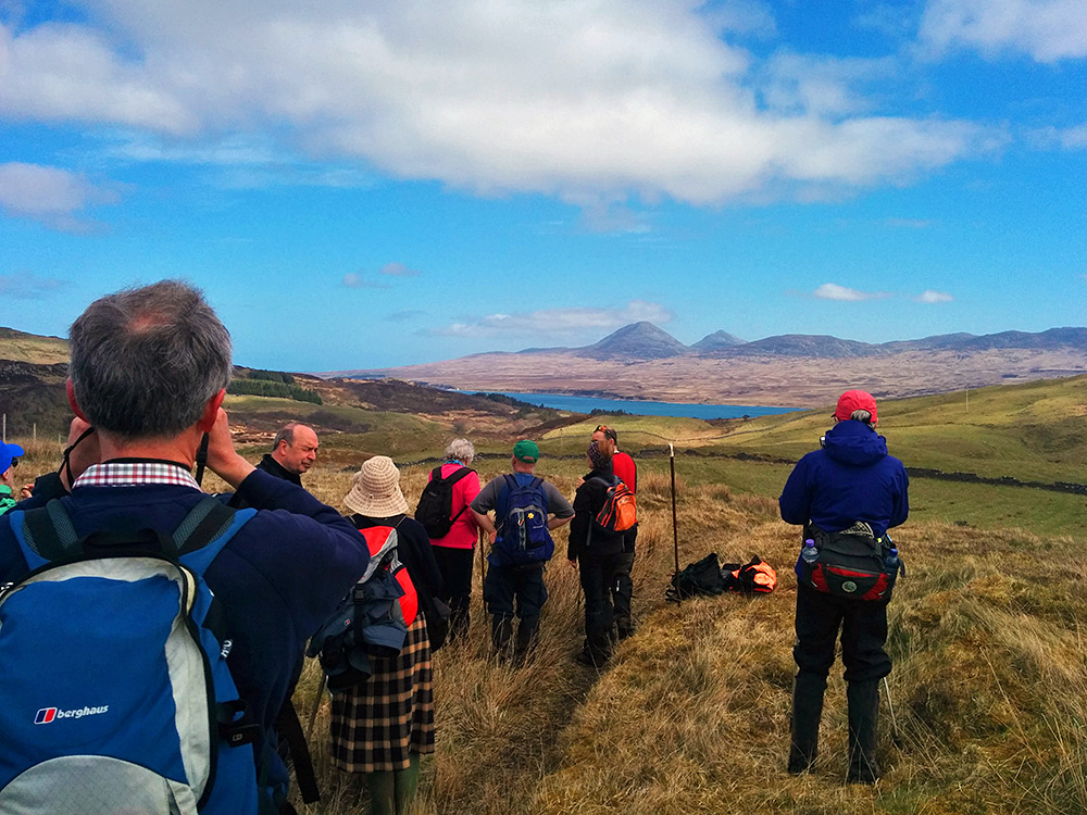 Picture of a group of walkers having briefly stopped above a sound between two islands