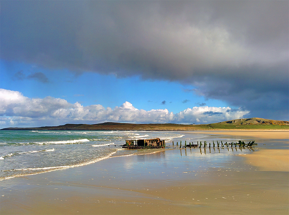 Picture of a wreck in a beach with some hills and a farm behind