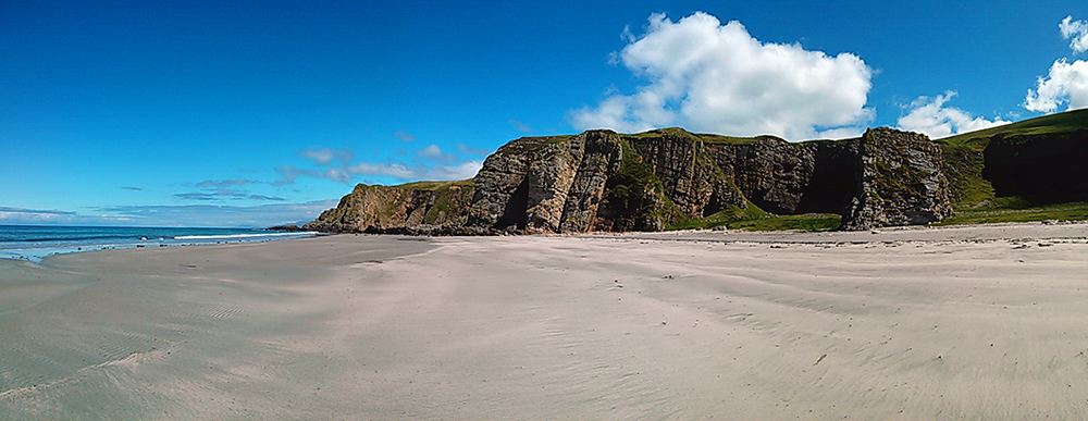Panoramic picture of a wide sandy beach below some steep cliffs