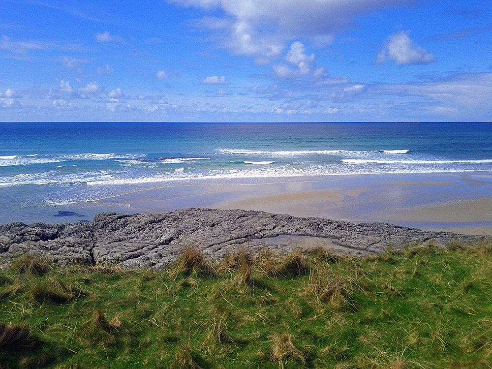 Picture of a view from a coast out to sea with grass, rocks, beach, waves, ocean, clouds and sky (in that order)