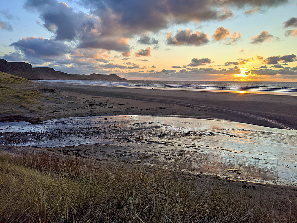 Picture of a November sunset over a bay with a beach seem from some low dunes