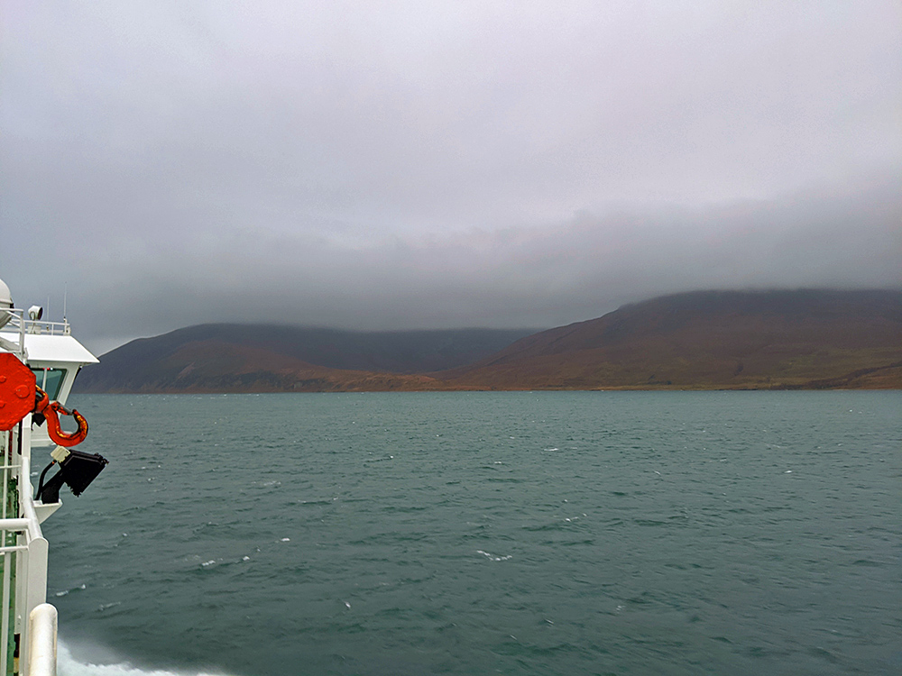 Picture of a ferry cruising along a sound on a cloudy day