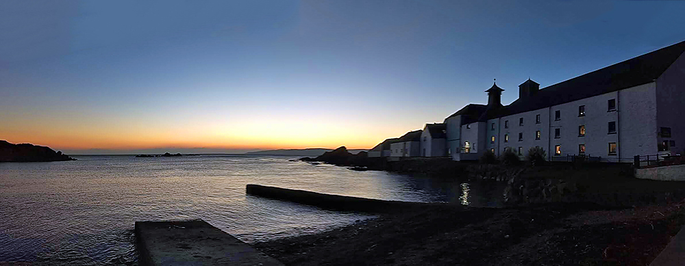 Panoramic picture of the gloaming at a coastal distillery at a small sea loch