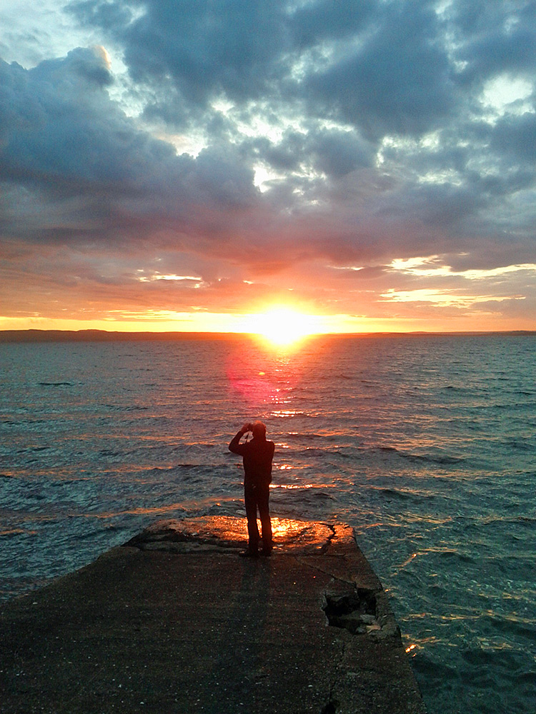 Picture of a man photographing a sunset from a slipway at a sea loch