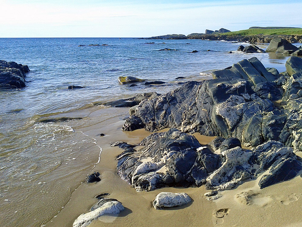 Picture of a shoreline with beach and rocks on a calm day