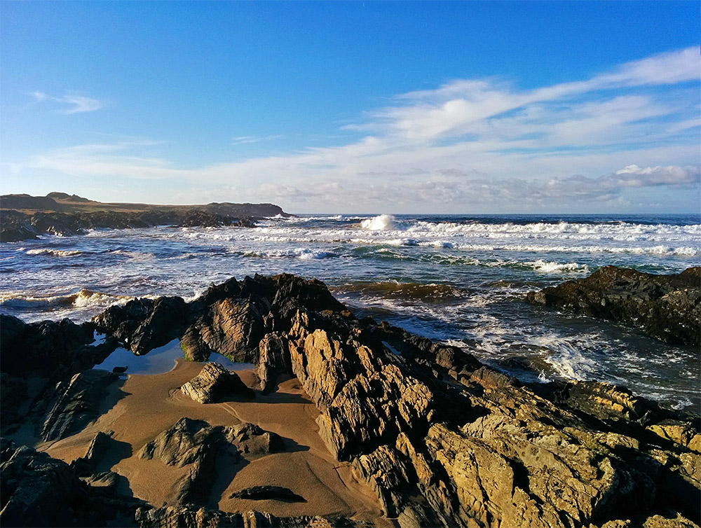 Picture of waves rolling into a bay with a rocky shore and some sand on a beautiful sunny November day