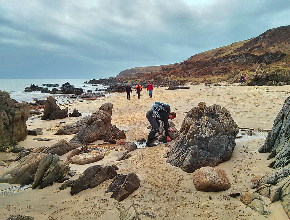 Picture of some walkers on a beach with some rocks