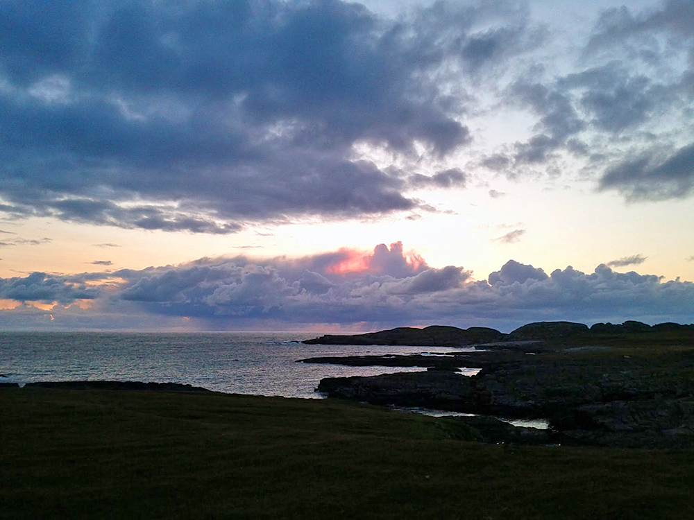 Picture of dramatic summer evening clouds of a rugged coastline