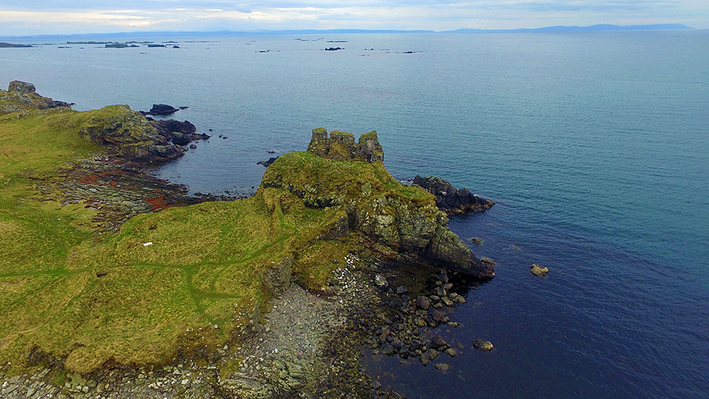 Aerial picture of the ruin of an old castle on a coast, skerries in the background