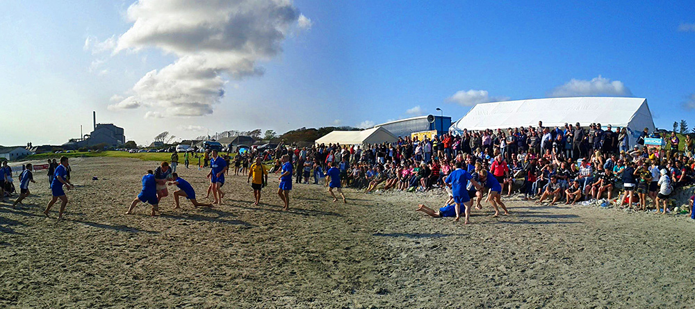 Panoramic picture of a beach rugby game with some movement duplication