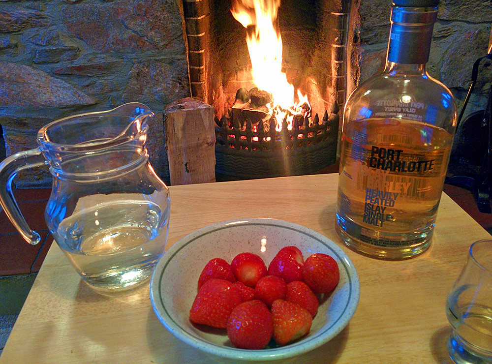 Picture of a table with Islay single malt whisky and Scottish strawberries in front of an open fire in a fireplace