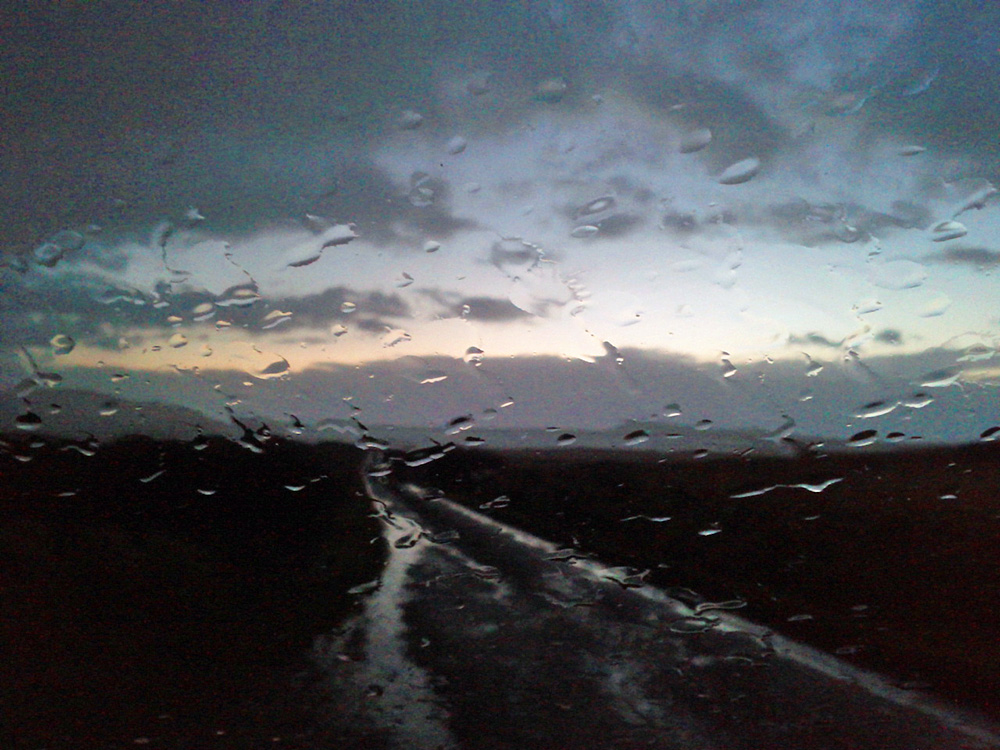 Picture of rain on a car windscreen on a rural road