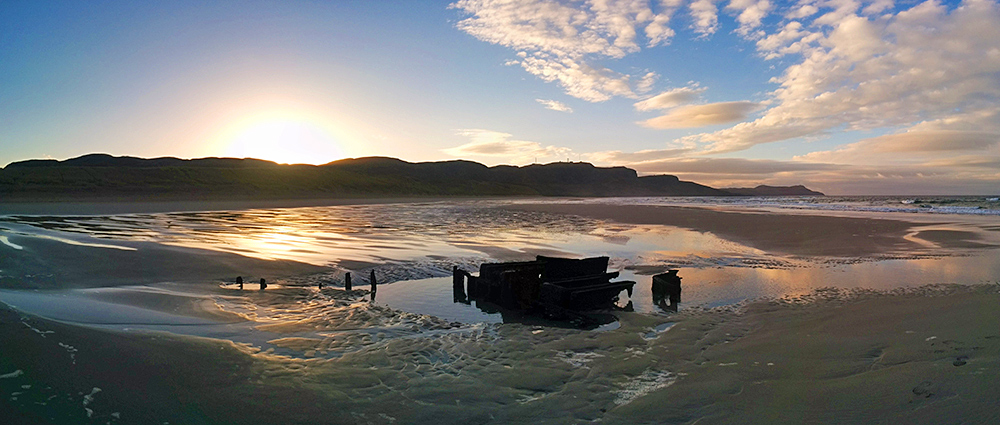 Panoramic picture of a sunrise over dunes/crags seen from a beach with a wreck