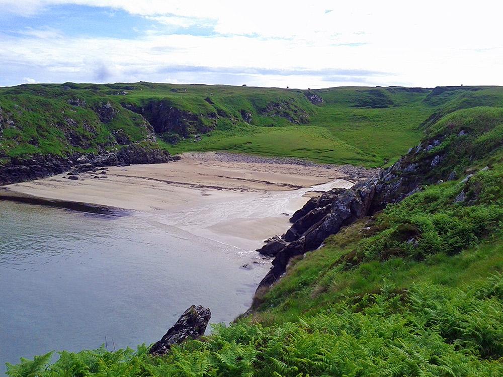 Picture of a small beach between cliffs, a shallow stream running across it