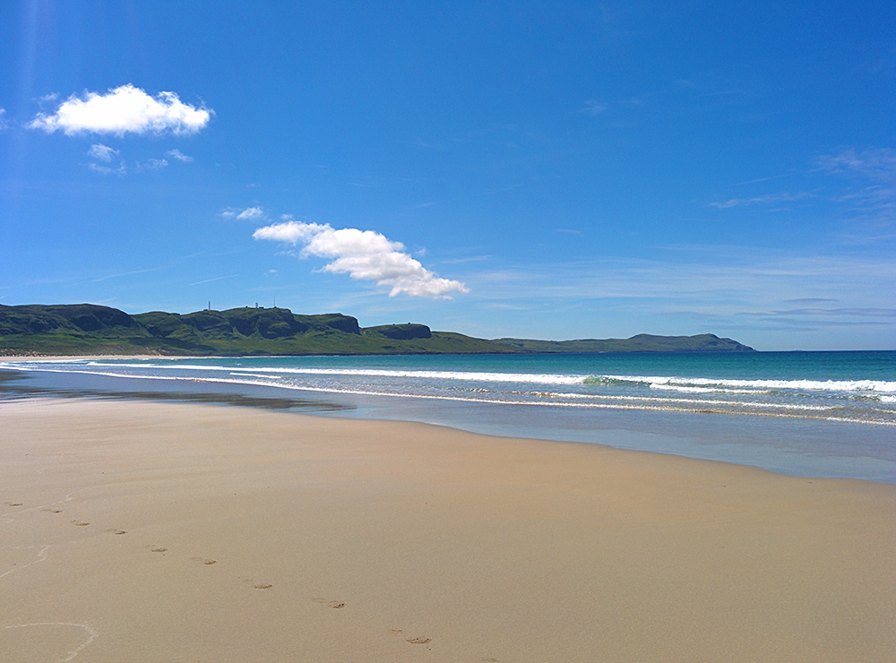 Picture of a sandy beach in a wide bay on a bright sunny June day