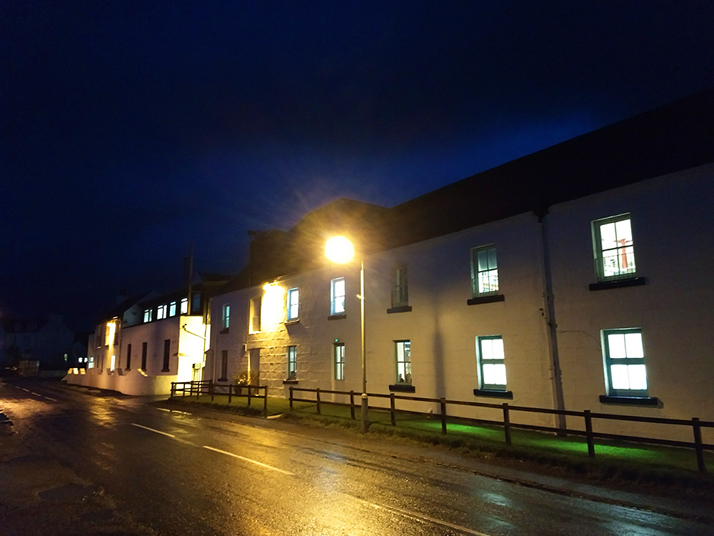 Picture of a whitewashed distillery building on a November evening