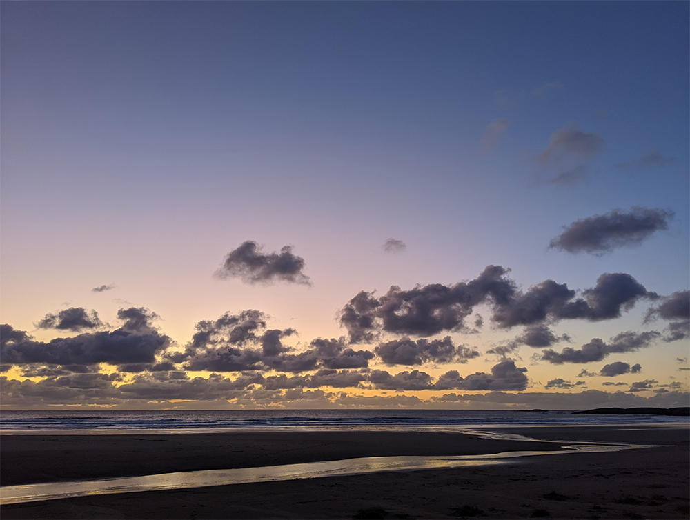 Picture of the gloaming seen from a beach, clouds in the distance, but clear skies above
