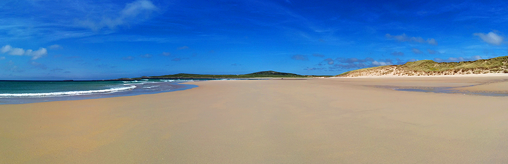 Panoramic picture of a wide sandy beach with some dunes
