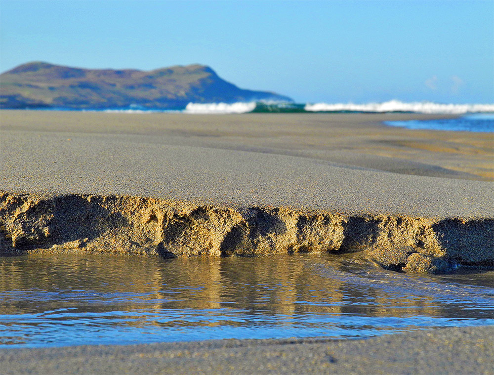 Picture of sand crumbling and breaking off at a small ridge on a beach