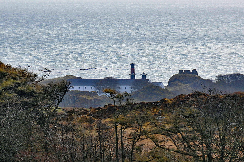 Picture of a coastal distillery (Lagavulin on Islay) with the ruins of a castle (Dunyvaig) behind