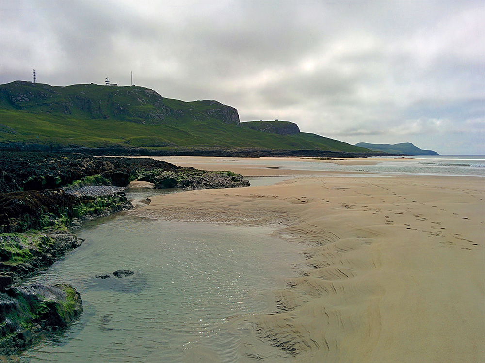 Picture of a beach at low tide under a cloudy sky