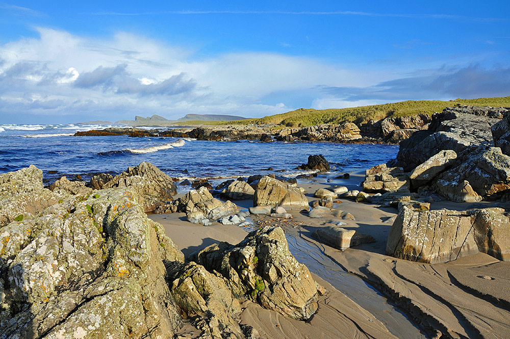 Picture of a coastal area with rocks and sand where a small river runs into the sea in a bay