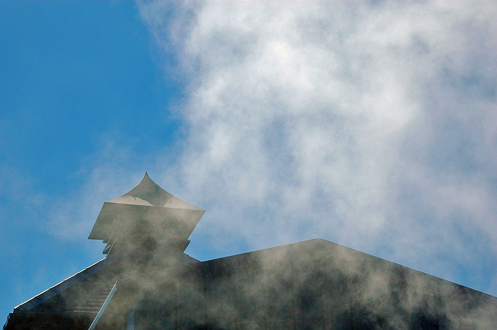 Picture of a distillery pagoda surrounded by smoke