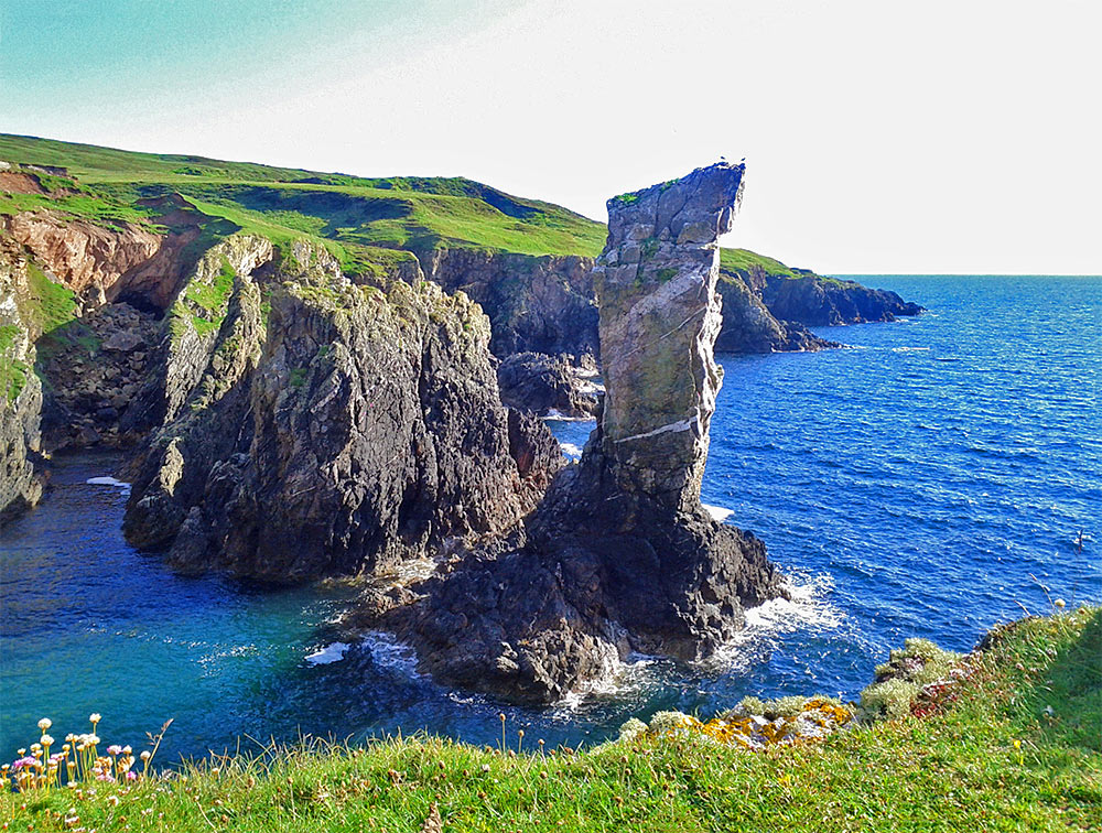 Picture of a sea stack in front of cliffs with bright sunlight behind it