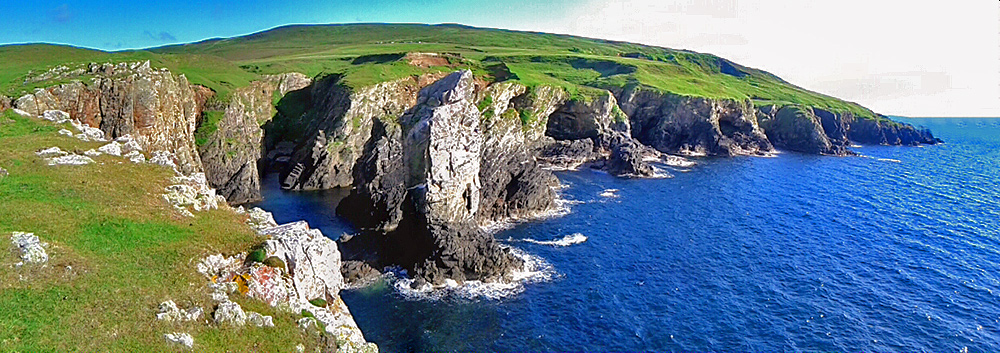 Panoramic picture of a sea stack in front of steep cliffs