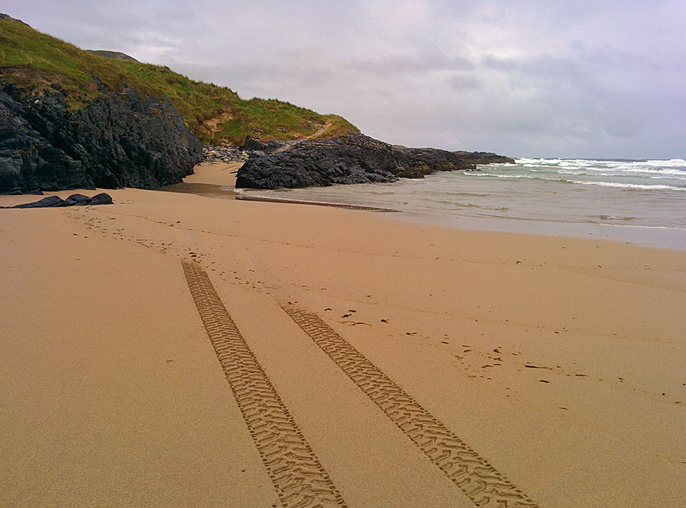 Picture of tyre tracks ending in nothing in the sand having been washed away by the tide